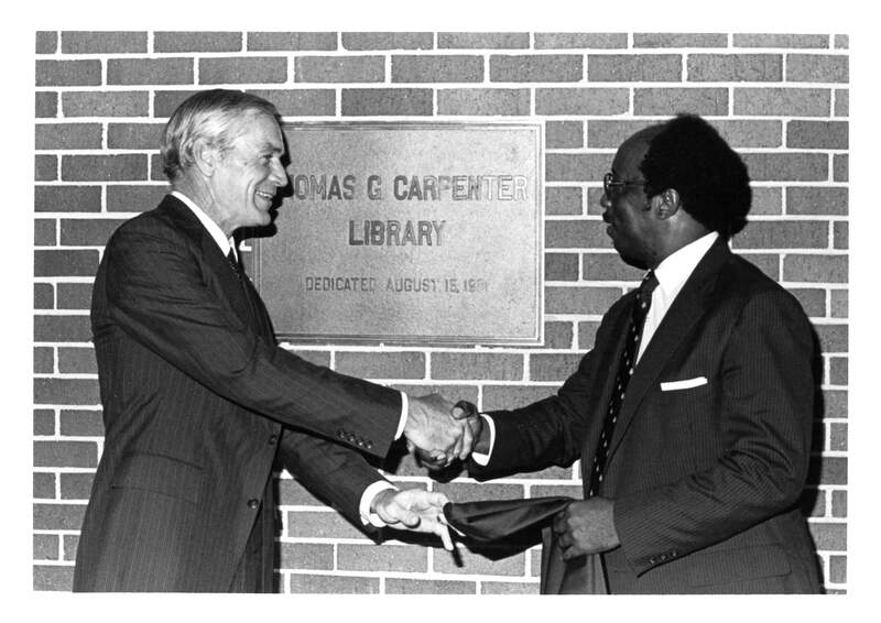 Presidents Thomas Carpenter and Andrew Robinson, shake hands at the dedication of the new Thomas G. Carpenter Library building on August 15, 1981.